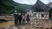 People in the village of Schultz in Ahweiler district are watching the devastation caused by the storm.  Photo: Harold Tittle / DPA