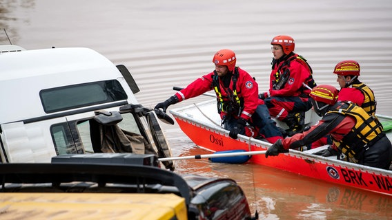 Erfstadt (North Rhine-Westphalia).  Water rescue workers use a boat to inspect trucks parked on flooded Federal Highway 265.  Photo: Marius Becker / DPA