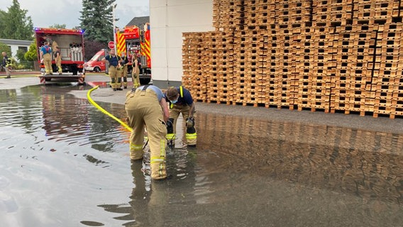 Two firefighters try to evacuate water collected in one place with euro boards.  © N.D.R.
