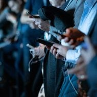 Many people are looking at their smartphone on the street.
