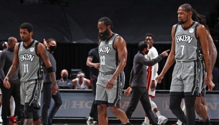 Les 3 superstars NBA des Brooklyn Nets, Kyrie Irving, James Harden et Kevin Durant, s'avancent la tête basse vers leur banc lors d'un match face au Miami Heat