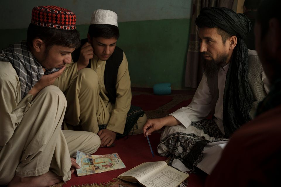 Afghan School Principal Sibghatullah Samadi, right, talks to students during class at a school in Kabul, ...