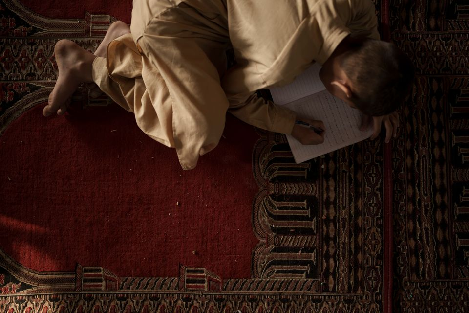 An Afghan student takes notes during class at a religious school in Kabul, Afghanistan, Tuesday, September 28, 2021...