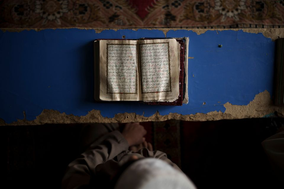 An Afghan student reads the Qur'an, Islam's holy book, at a religious school in Kabul, Afghanistan, Tuesday, September...